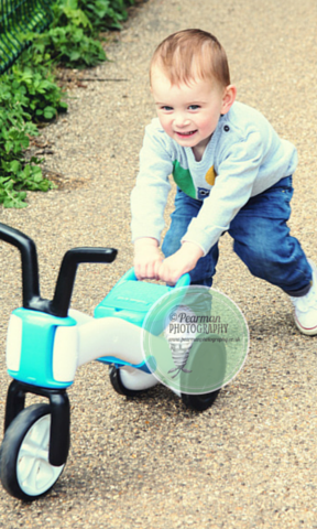 Toddler Joshua pushes his trike along with glee instead of the traditional method of sitting on it and riding it.