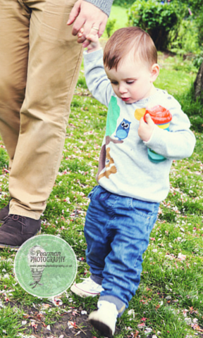 Joshua holding Daddy's hand and looking down at the cherry blossoms that have fallen to the park's grassy ground.