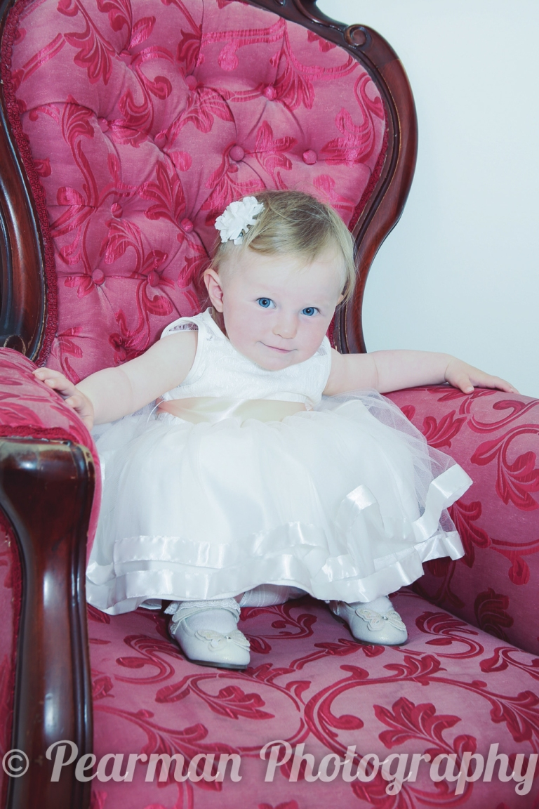 Flower girl sitting on a red vintage chair