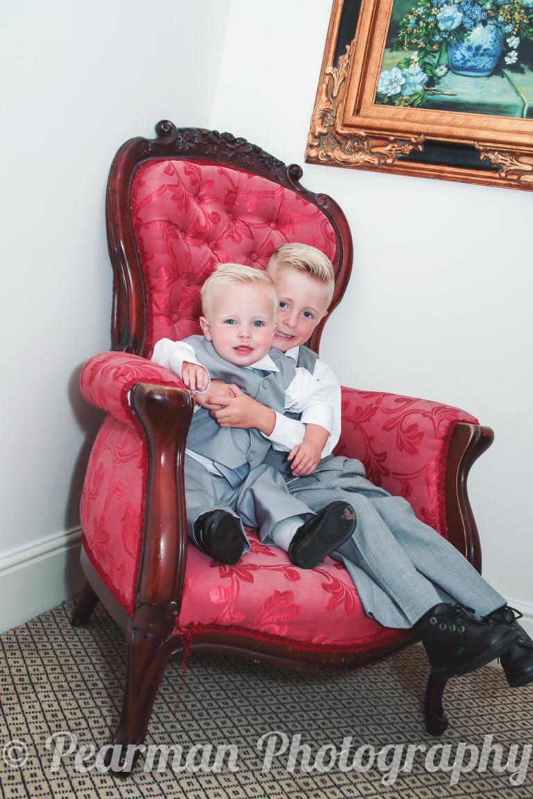 Brotherly Page Boys Sitting on a Red Vintage Chair hugging