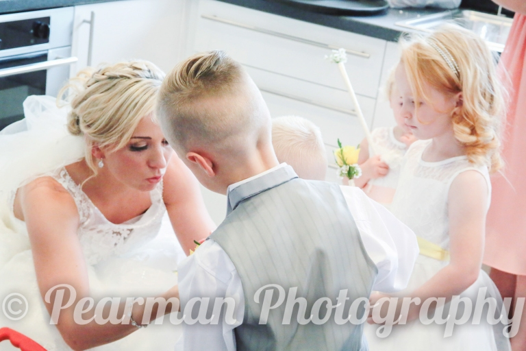 Bride putting on a buttonhole to a small page boy