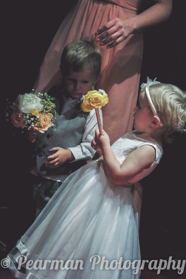A page boy and a flower girl waiting in the dark scowling at each other before walking down the aisle