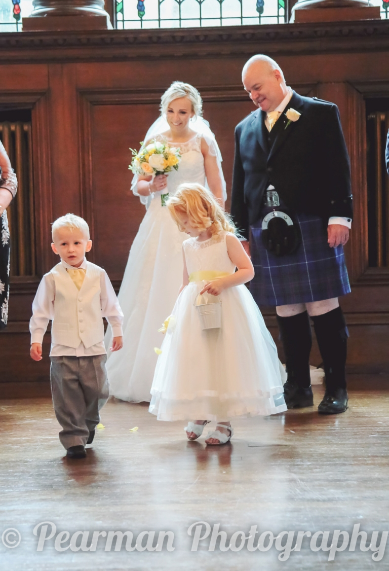 Bride looks on with pride at her children being page boy and flower girl