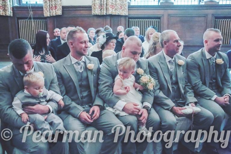 Smart groomsmen looking onto the ceremony