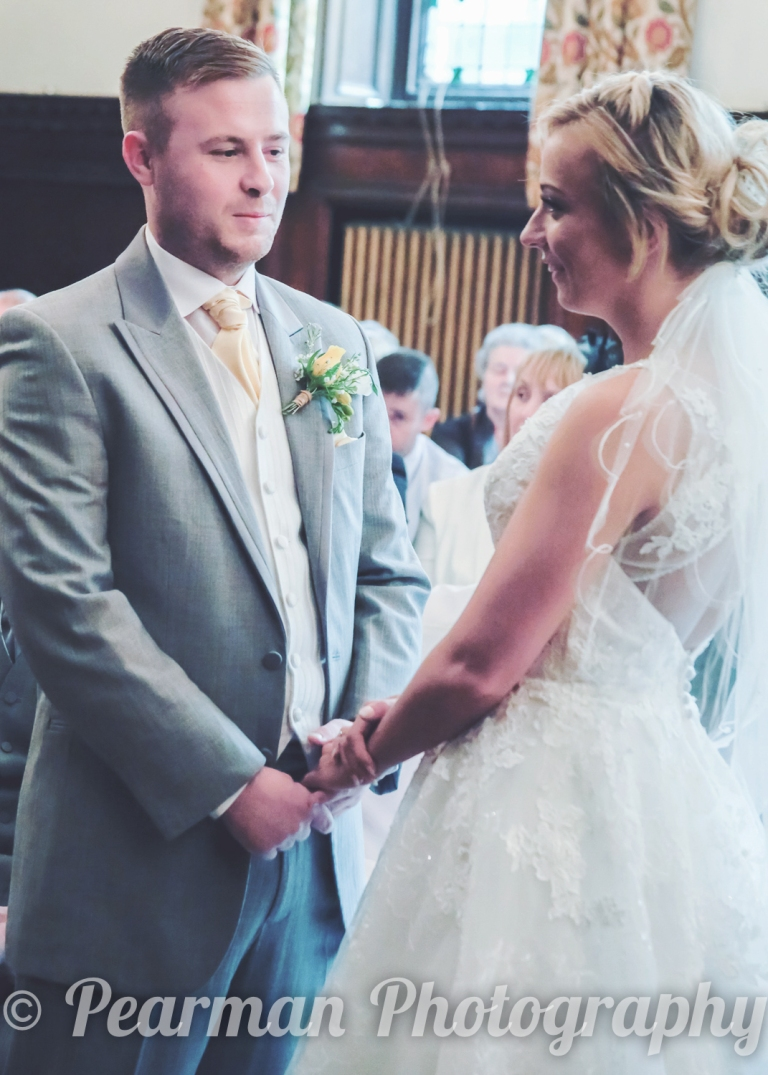 Bride and Groom holding hands and smiling whilst saying vows