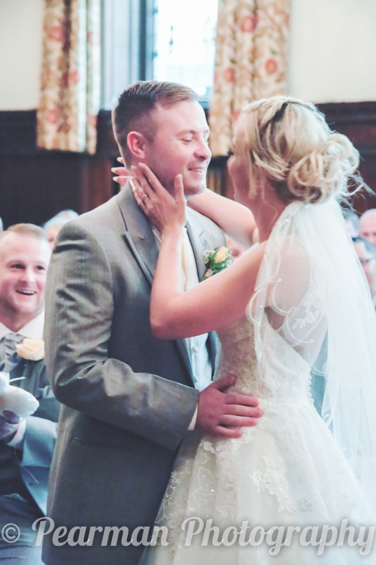 Bride touches Grooms face before they kiss