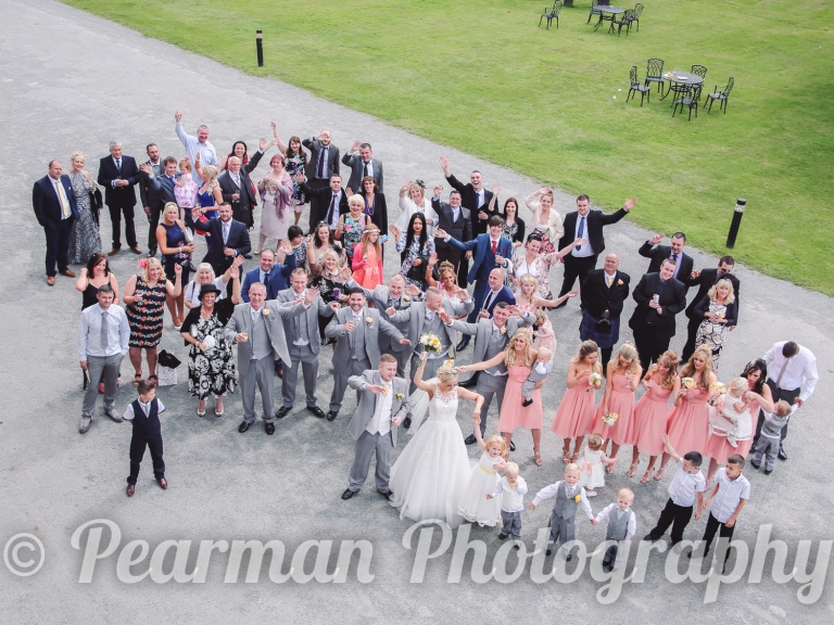 An aerial shot of the Wedding party all waving at the photographer