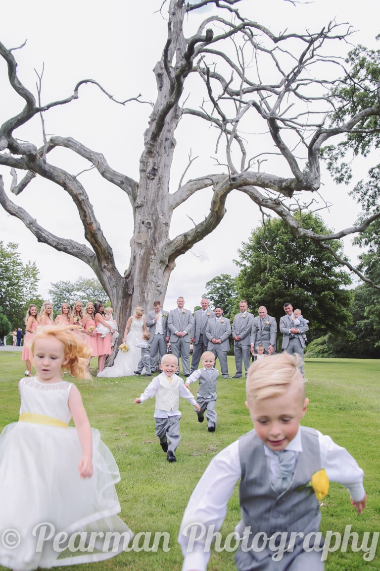 Children running toward the camera in a traditional wedding set-up