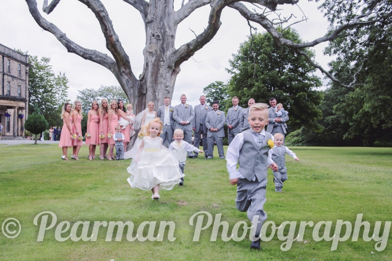Children running toward the camera in a traditional wedding set up