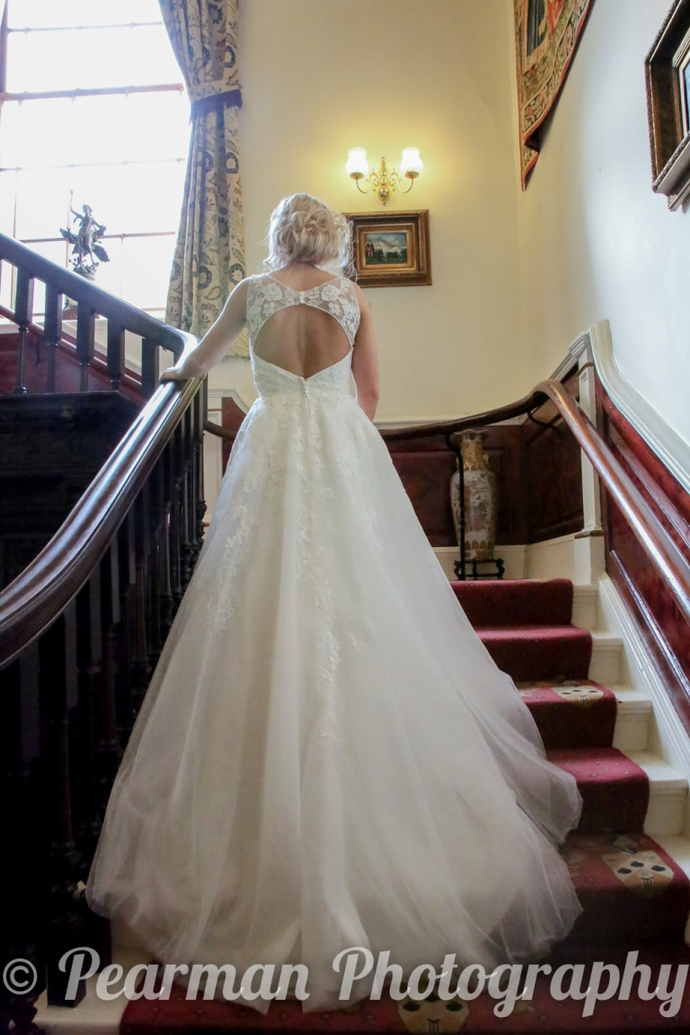 Bride standing on stairs showing the train of her gown
