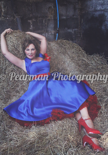 Laying down in a pile of hay inside her stables, Trish wears a Red and Blue Swing Dress.