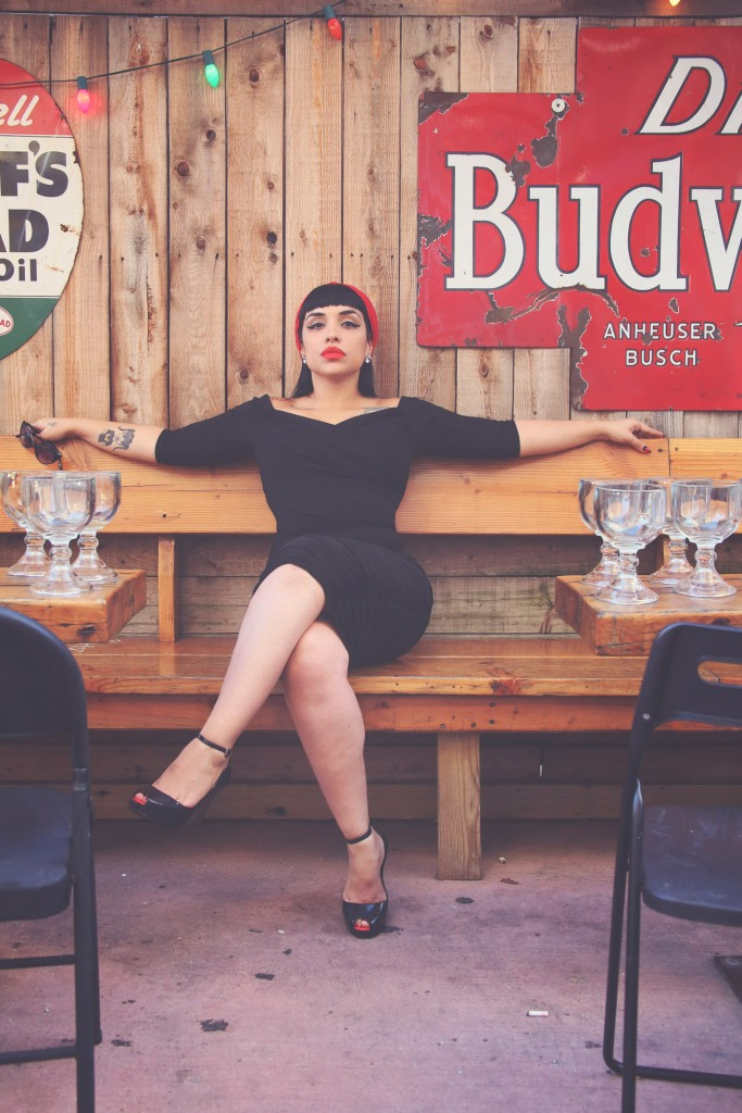 Hot Latina pin-up posing crossed legs in Brooklyn outdoor bar with wooden walls
