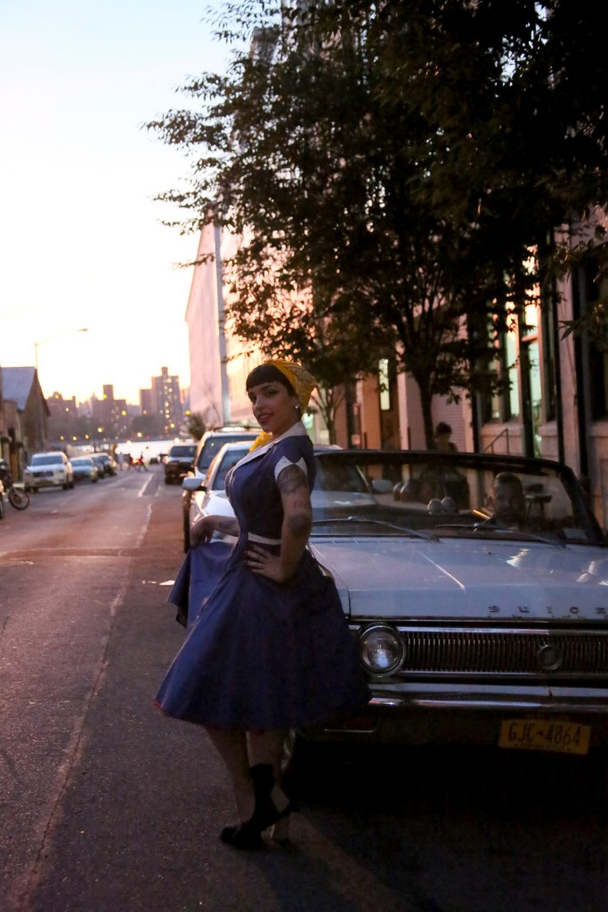 Pin-Up sits on a beaten up buick in the sunset on a Brooklyn Street.