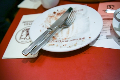 An empty plate with tiramisu crumbs on it in a cafe.