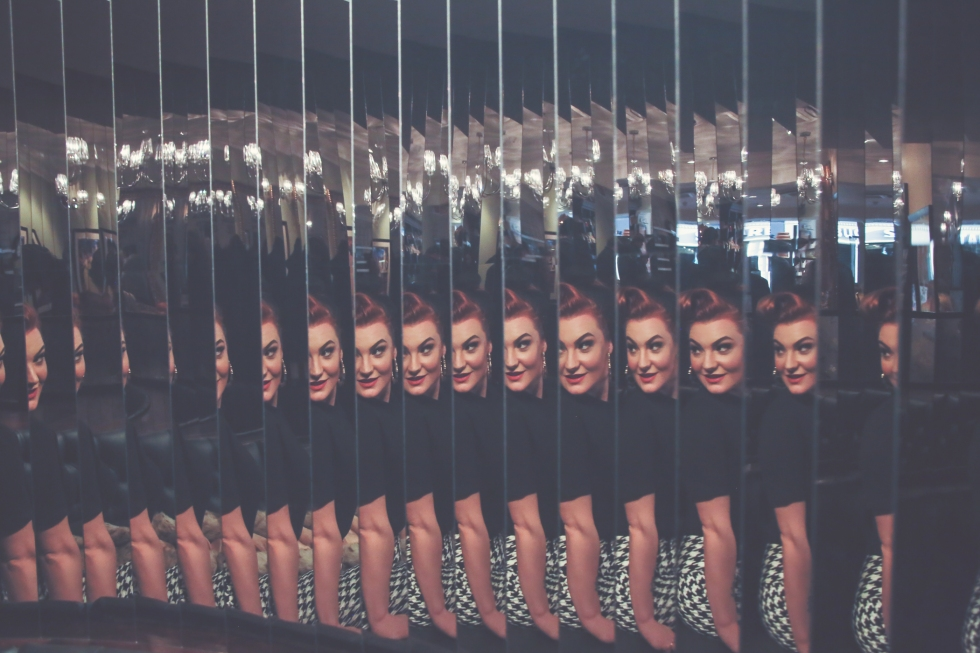 Multiple reflections of the same girl in the same pose using cut glass