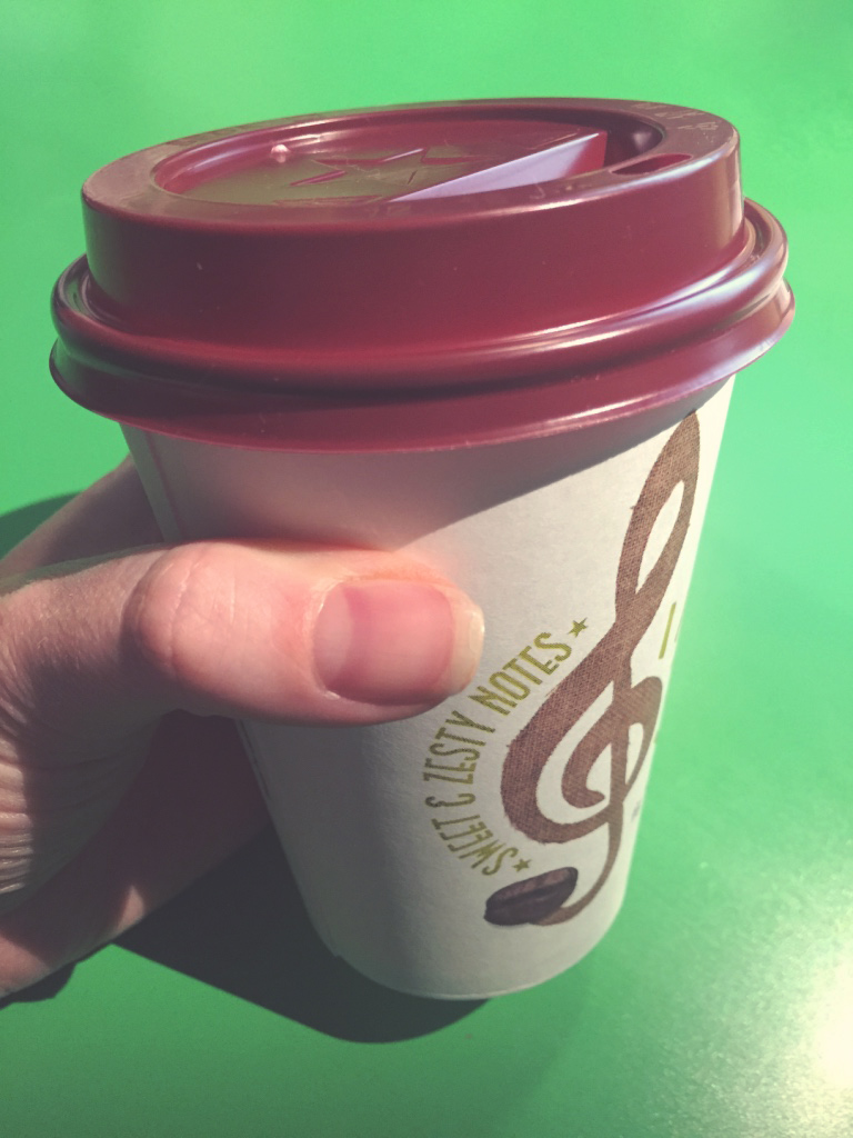 A cup of coffee being held by a hand for the photograph.