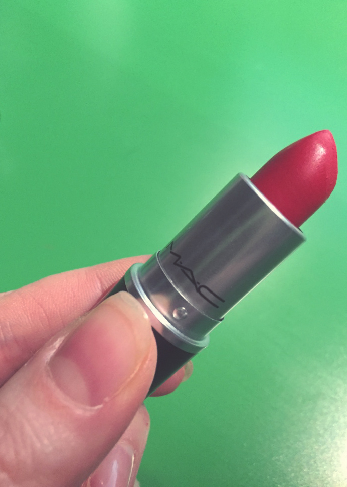 Red lipstick by mac, with a hand holding it for the photograph